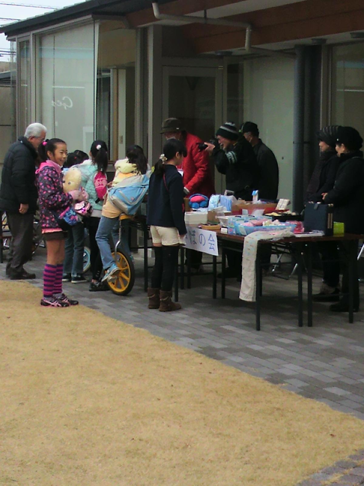 お祭りで年配の方々のバザーに集まる子供と年配の方々の笑顔