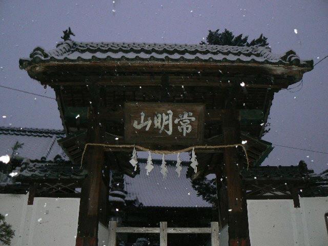 雪が舞う山門
