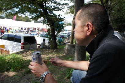 豚串をほおばってオリオンビールを飲むテツ。暑いからビールがおいしいっ
